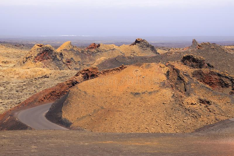 Curved road between rugged red mountains - Timanfaya NP, Lanzarote stock photo