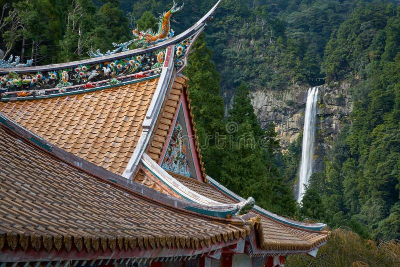 Curved roofs of colorful Chinese temple and Nachi waterfalls on the background. Wakayama. Japan. The curved roofs decorated with ornamental dragons at the royalty free stock photos