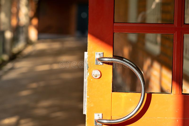 Curved steel handle on a wooden door. Curved steel handle on an open wooden door in sunlight in a close up view with copy space royalty free stock photo