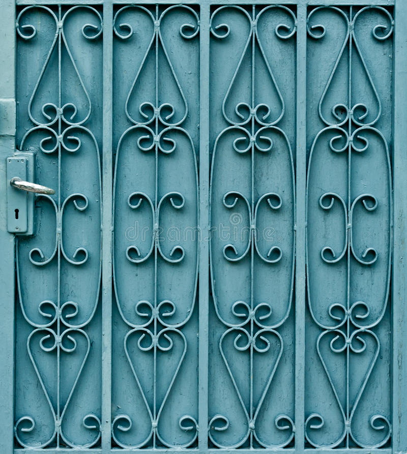 Curved steel pattern on door with handle. Curved pattern design on green metal door with handle stock images