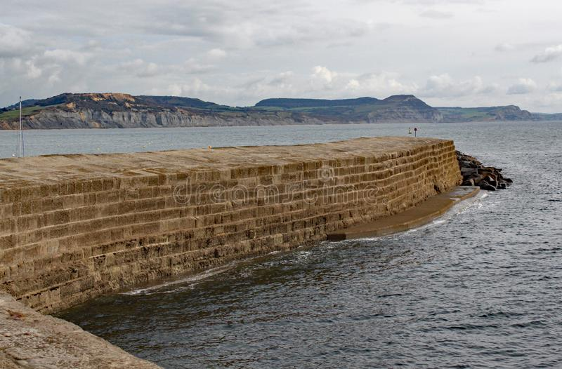 The curved wall of the Cobb at Lyme Regis, Dorset in England stock photography