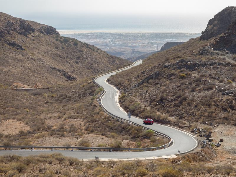 Curved winding road with a red car in the mountains in Gran Canaria royalty free stock photo