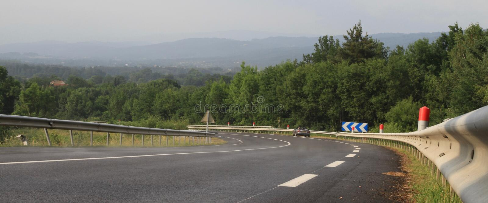 Curving black road, armco and Curving black road, armco and cevrons in the Massif Central in in the Massif Central in. Curving black road, armco and chevrons in stock photo