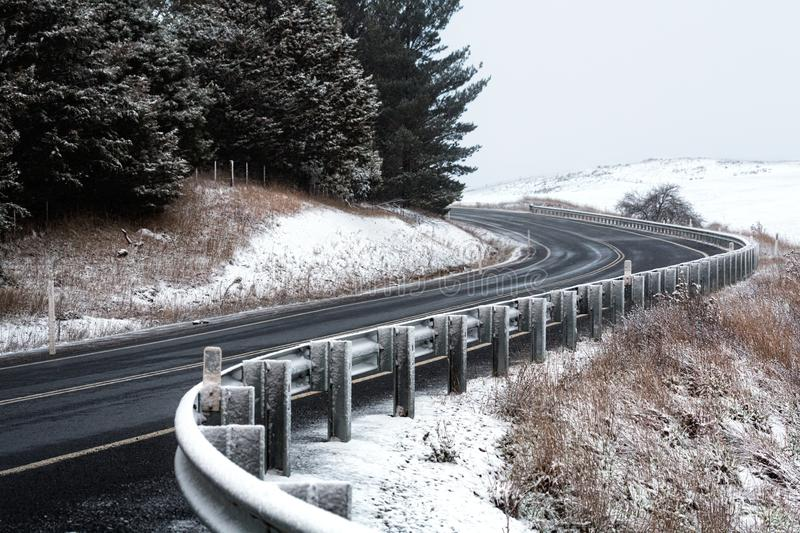 Curving road through snow covered hills stock image
