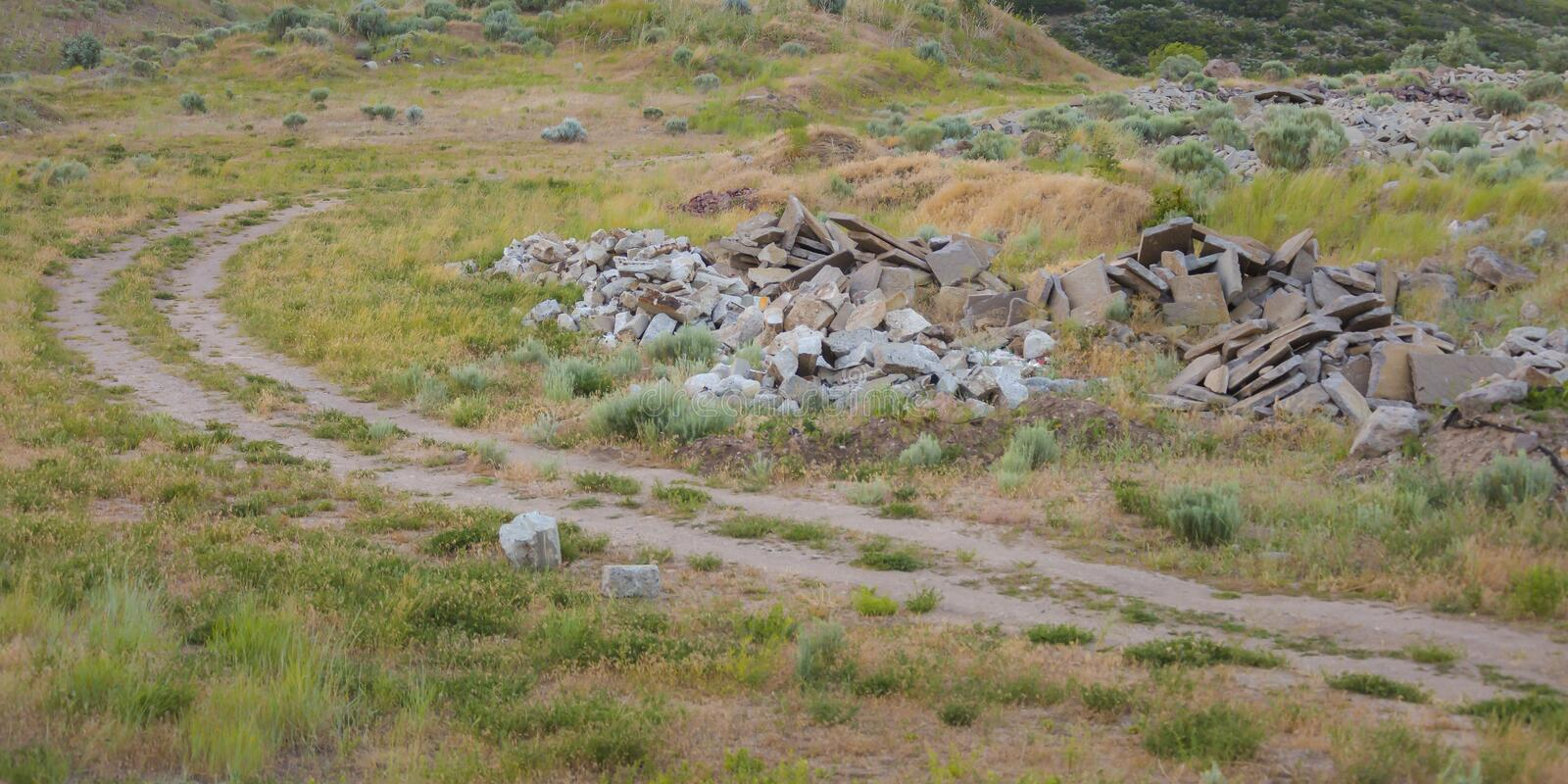 Curving trail on a grassy ground with piled stones stock photo