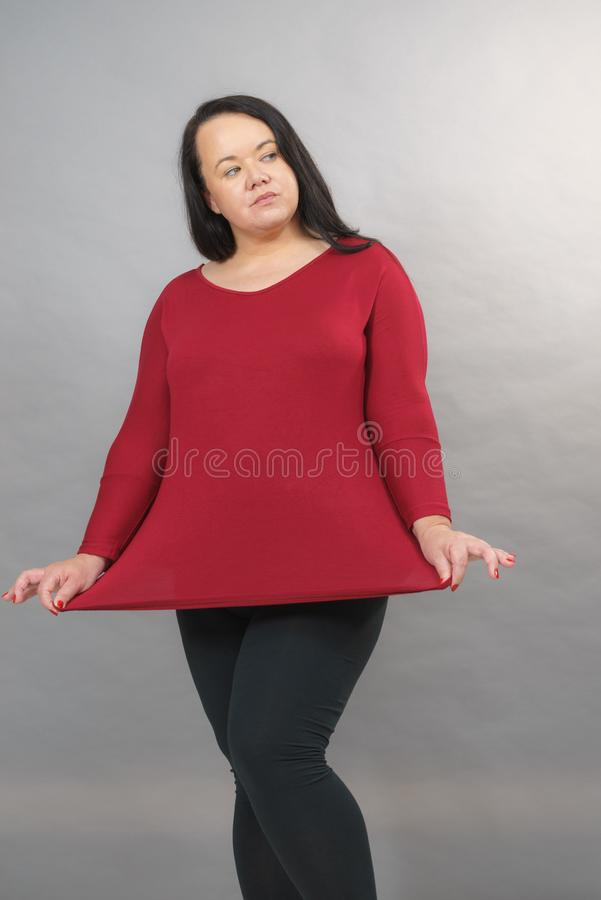 Woman showing size of red top tunic. Curvy adult woman showing showing plus size of red long cotton elastic top tunic. Mature fashion, clothing, style concept stock photos