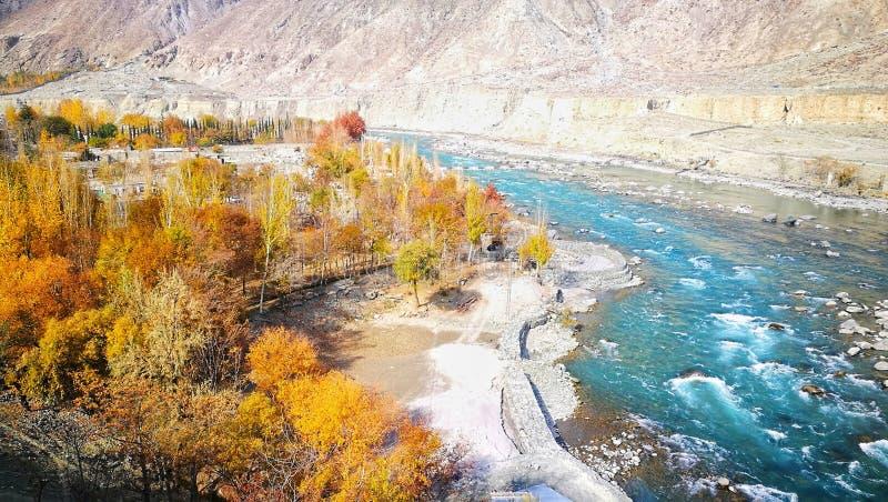 Curvy błękitna turkusowa rzeka i kolor żółty opuszcza w jesieni z rockowym halnym tłem zdjęcie stock