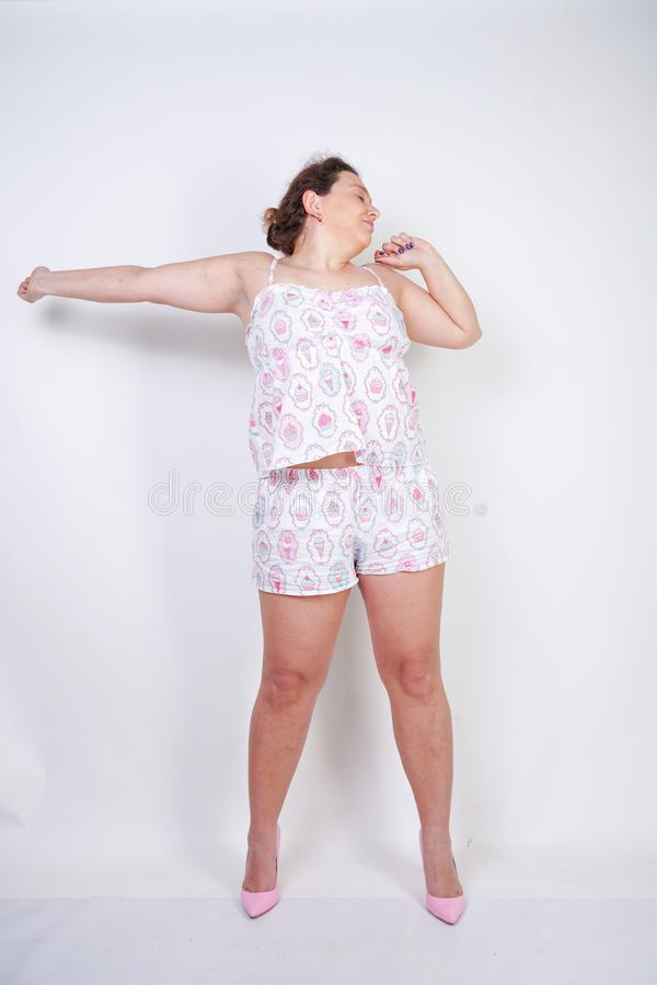 Curvy chubby woman in funny pajamas stands and stretchintg on a white background in the Studio stock image