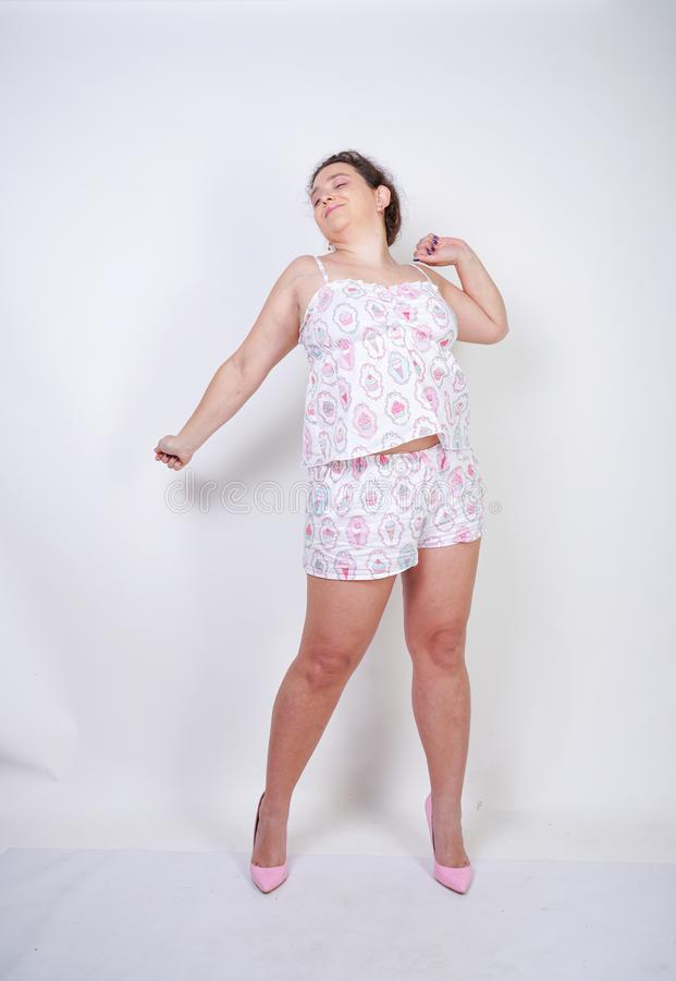 Curvy chubby woman in funny pajamas stands and stretchintg on a white background in the Studio royalty free stock images
