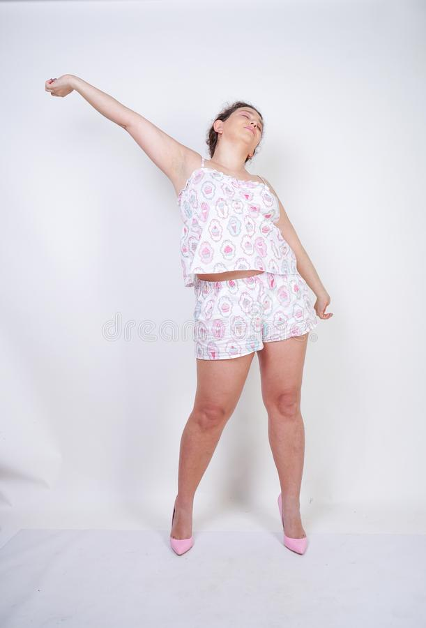 Curvy chubby woman in funny pajamas stands and stretchintg on a white background in the Studio stock photography