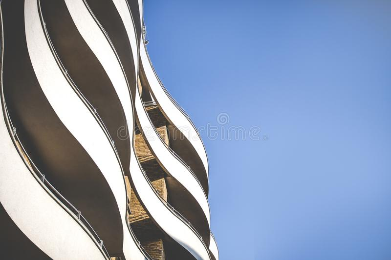 Curvy elegant building with brick facade blue sky in the background stock photo