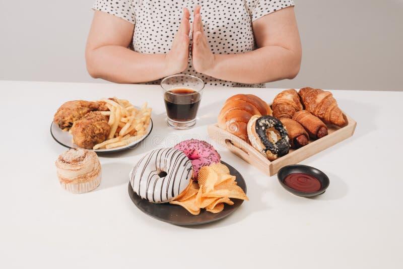 Curvy female preparing to eat hamburger, overeating problem, depression.  stock photography