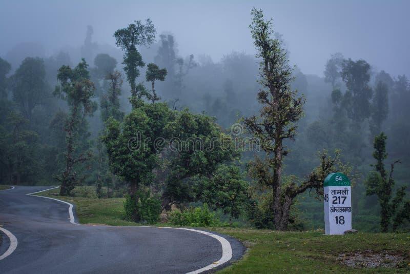 Curvy Himalyan halna droga z wysokimi drzewami zakrywającymi w mgle i kamieniu milowym zdjęcia royalty free