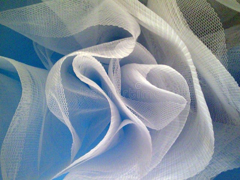 Curvy mesh material. Blue dress. Festive blue dress from below. Curvy white mesh material. Optical stock photo