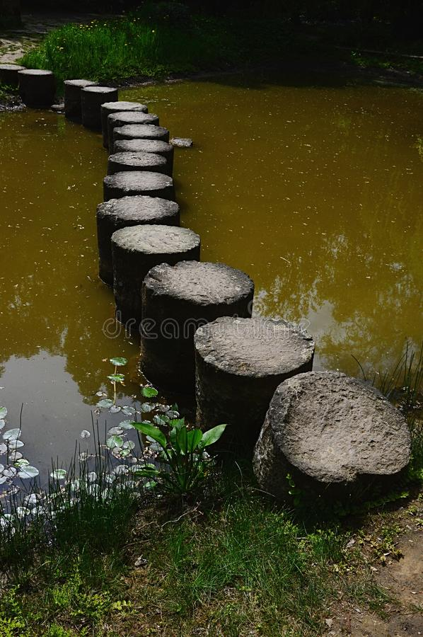 Curvy pathway through the muddy decorative pond made of barrel shaped stone columns stock photography