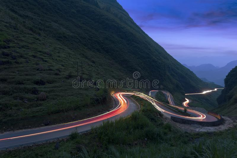 A curvy road through the grassy hills at twilight. stock images