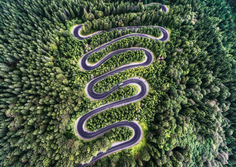 Curvy road from the high mountain pass in Transfagarasan, Romania. Great road trip trough the dense woods. Aerial view royalty free stock photos