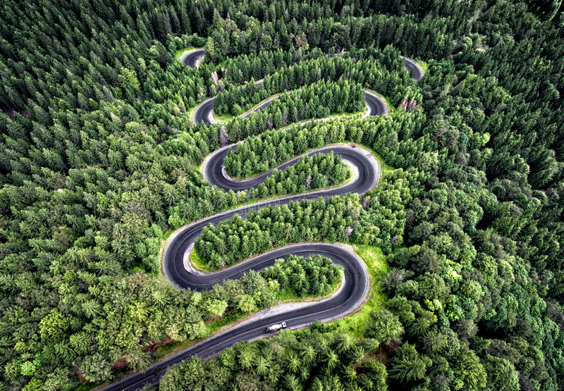 Curvy road from the high mountain pass in Transfagarasan, Romania. Great road trip trough the dense woods. Aerial view royalty free stock photography