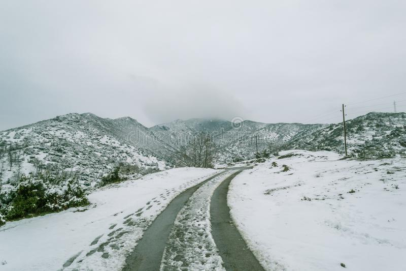 Curvy road in the snow. Curvy road, in the snow, winter cloudy day, in the mountains stock image