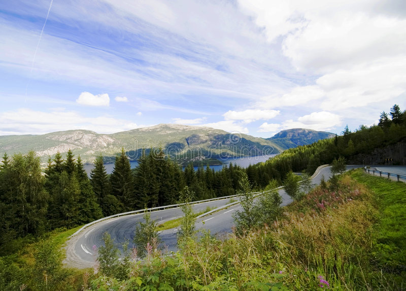 Curvy roads of Norway. Telemark county, Norway. A sight of curvy roads leading up the mountain, fjord water in the distance stock photography