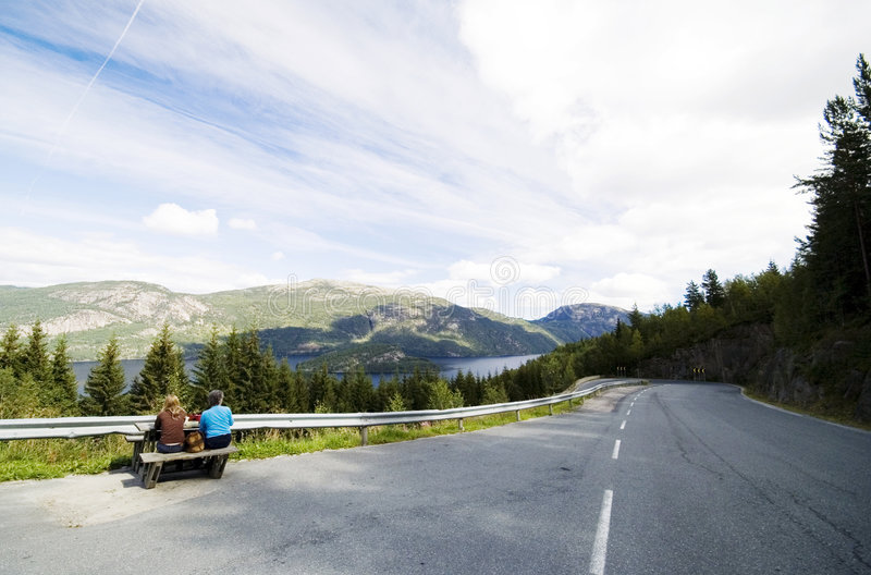 Curvy roads of Norway. Telemark county, Norway. Two women sitting at a table, having a meal, looking at the landscape around royalty free stock photography