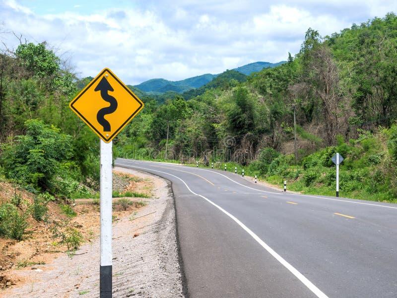 Curvy vägmärke till berget royaltyfri foto