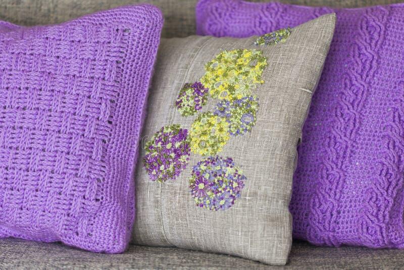 Cuscini decorativi - la viola tricottata con le trecce appoggia ed appoggia fatto di tessuto di tela con ricamo variopinto fotografia stock