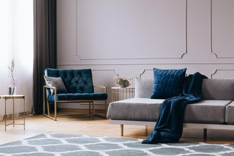 Cuscini e coperta sul sofà moderno nell'interno luminoso del salone immagine stock