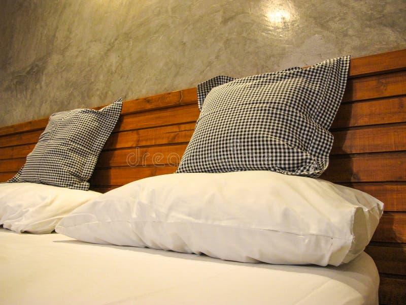 Cuscini e cuscino di tiro sul letto bianco fotografia stock