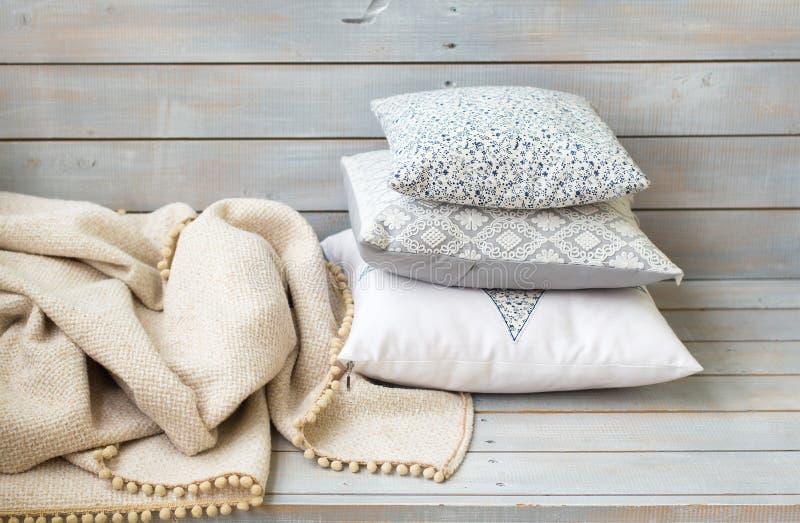 Cuscini e plaid sui precedenti di legno leggeri immagine stock libera da diritti