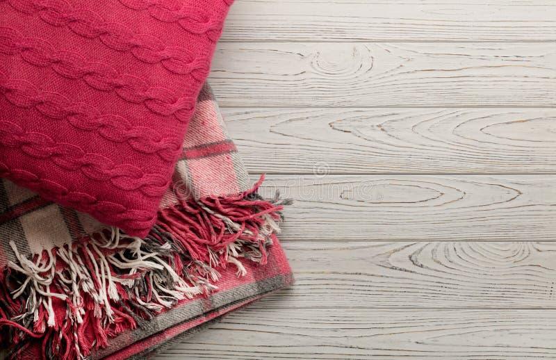 Cuscini e plaid tricottati su un fondo di legno leggero immagini stock libere da diritti