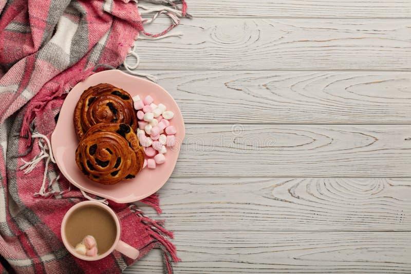 Cuscini e plaid tricottato, panini e caffè su un BAC di legno leggero immagine stock