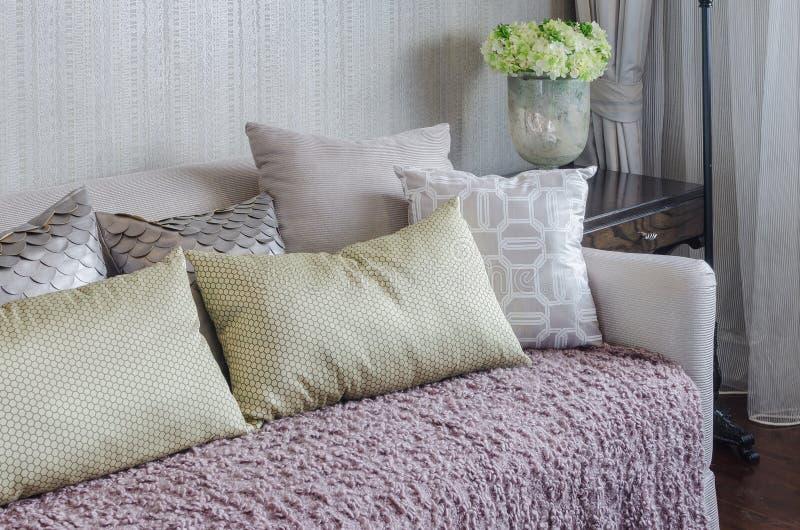 Cuscini gialli sulla coperta rosa sul sofà di lusso in salone fotografia stock