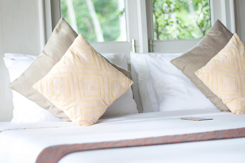 Cuscini, letto dalla finestra nella camera da letto fotografia stock