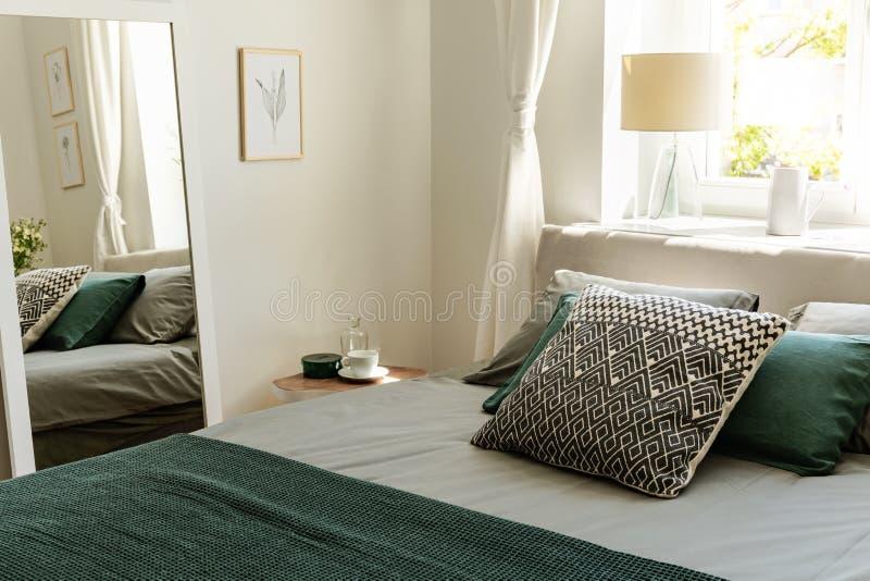 Cuscini modellati e verdi sul letto nei wi interni della camera da letto semplice immagini stock libere da diritti