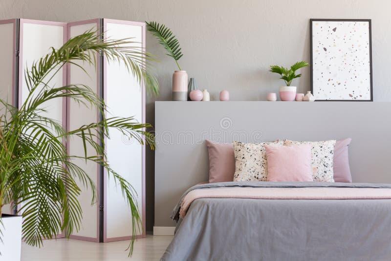 Cuscini rosa sul letto grigio nell'interno pastello della camera da letto con la palma ed il manifesto su bedhead Foto reale immagini stock