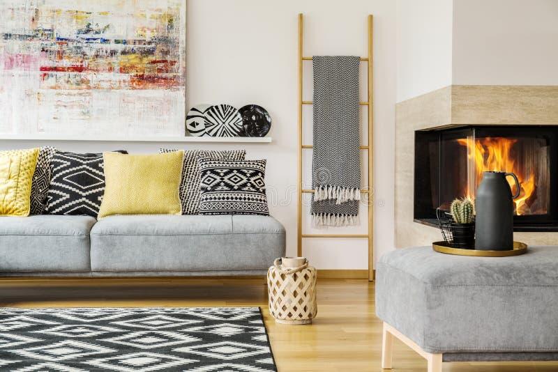 Cuscini sul divano grigio nell'interno caldo del salone con il paintin fotografia stock