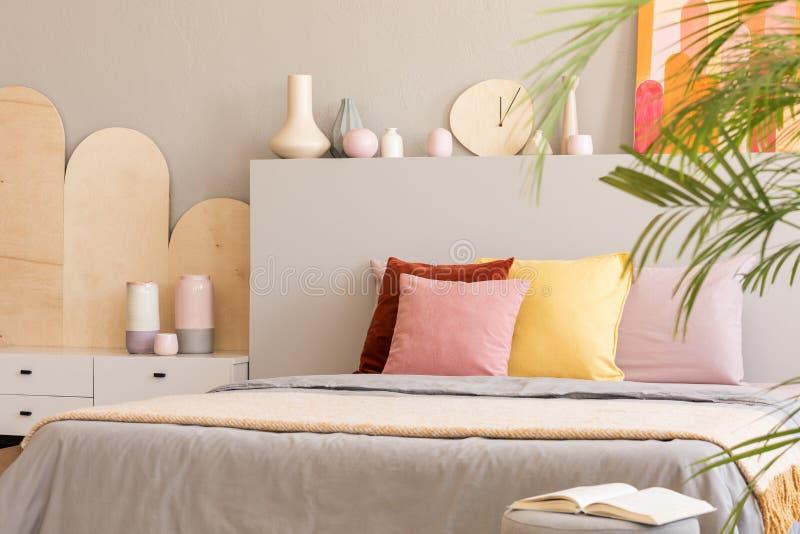 Cuscini variopinti sul letto con la testata accanto al gabinetto nel grey fotografie stock