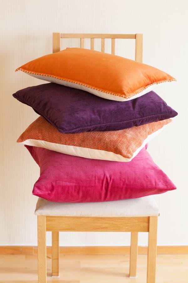 Cuscini variopinti sull'umore domestico accogliente della sedia immagini stock