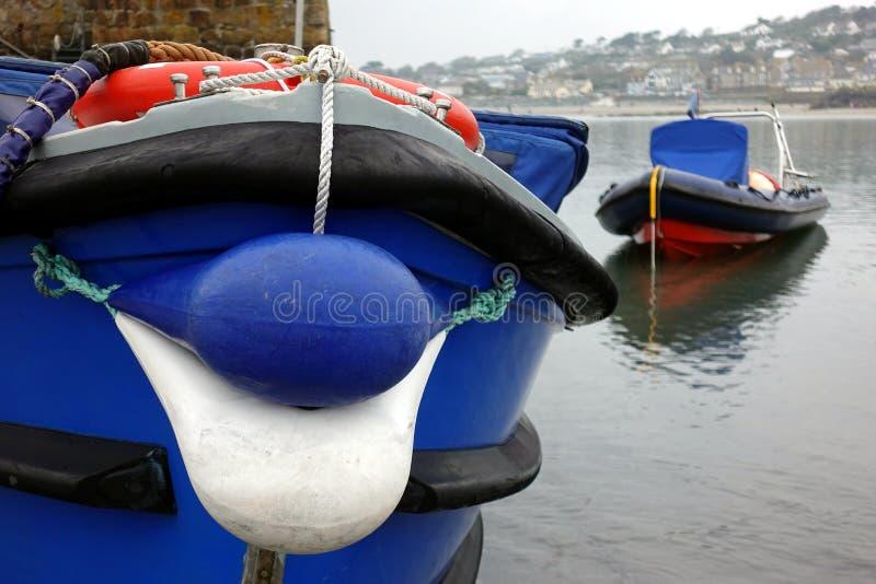 Cuscino ammortizzatore o boa blu luminoso che protegge la parte anteriore di una piccola barca fotografie stock