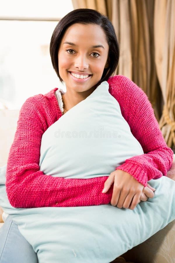 Cuscino castana sorridente della tenuta fotografia stock