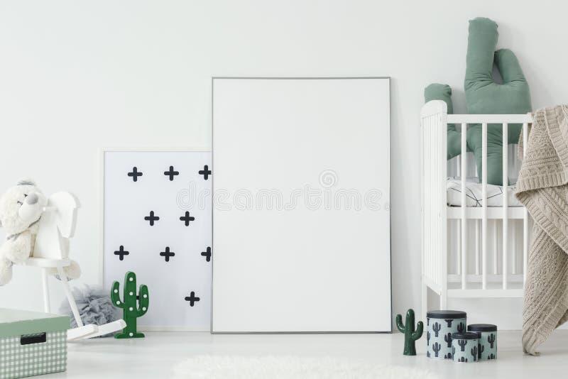 Cuscino del cactus in culla bianca accanto al manifesto vuoto con il modello i immagine stock