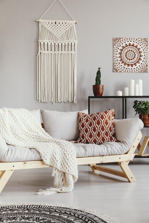 Cuscino e coperta modellati sul sofà nel salone di boho Foto reale immagine stock libera da diritti
