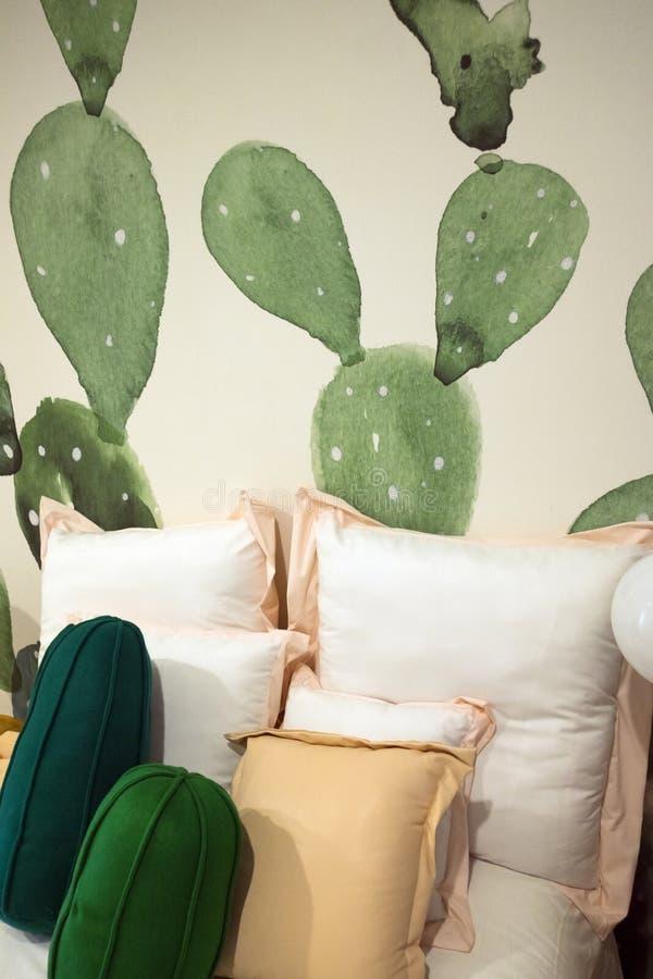 Cuscino e cuscini sul letto nella stanza della pittura del cactus interno fotografie stock
