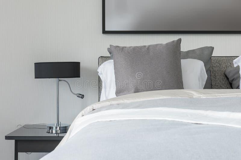 Cuscino grigio sul letto bianco in camera da letto moderna for Camera letto nera