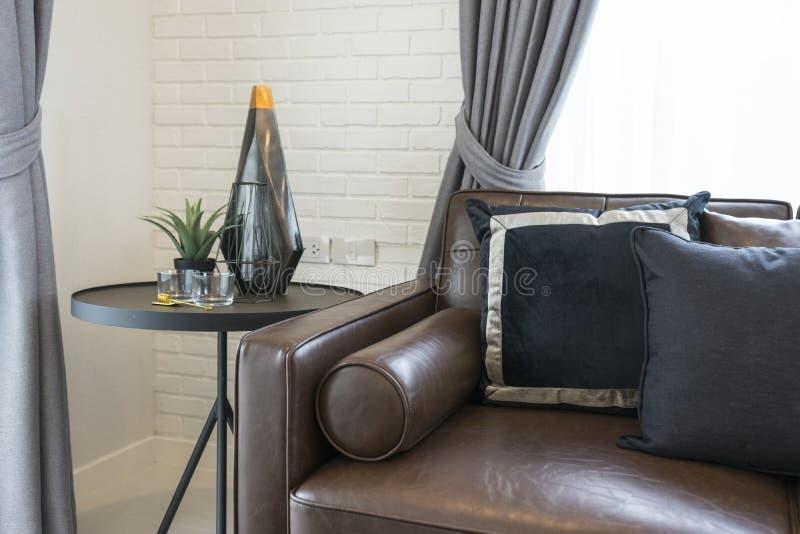 Cuscino nero e grigio di lusso sul sofà in salone con la tavola laterale fotografie stock