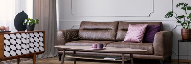 Cuscino rosa sul divano di cuoio nell'interno del salone con la pianta sull'armadietto vicino alla tavola Foto reale fotografia stock