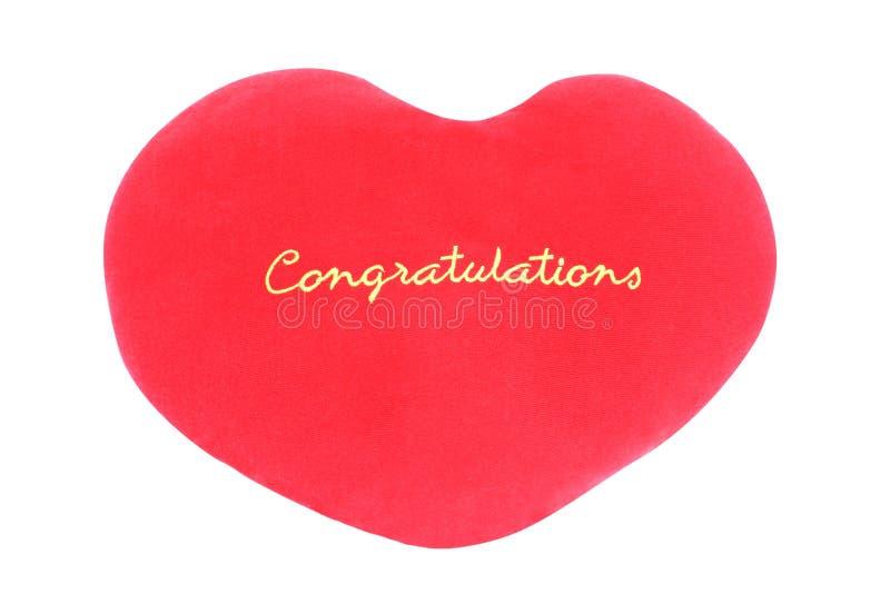 Cuscino rosso con le congratulazioni del messaggio isolato su fondo bianco immagini stock libere da diritti