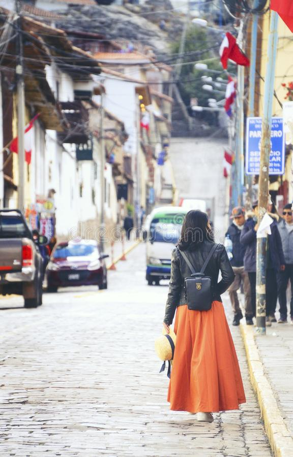 Cusco County, Peru - August 8th, 2018: A woman wearing an orange skirt and a hat walks on the steet in a old town of Cusco area in royalty free stock photography