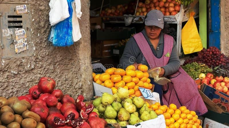 CUSCO, PERÚ 20 DE JUNIO DE 2016: una mujer empaqueta los mandarines frescos en un mercado en cuzco imagen de archivo